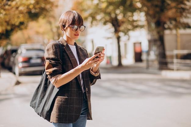 Mulher jovem atravessando uma rua usando o telefone