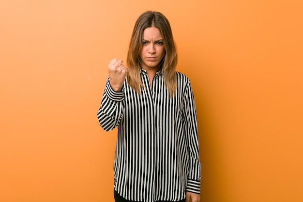 Mulher jovem autêntica carismática de pessoas reais contra uma parede mostrando o punho para a câmera, expressão facial agressiva.