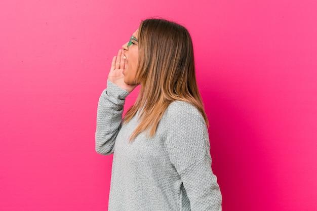 Mulher jovem autêntica carismática pessoas reais, gritando e segurando a palma da mão perto da boca aberta.