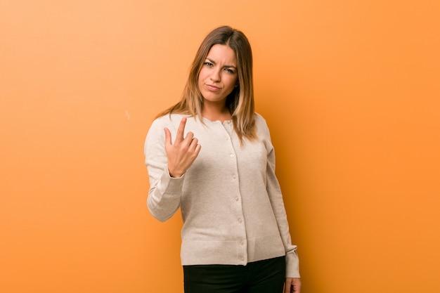 Mulher jovem autêntica e carismática de pessoas reais contra uma parede apontando com o dedo para você como se estivesse convidando para se aproximar.