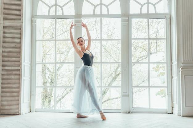 Mulher jovem bailarina clássica na aula de dança. a bailarina graciosa bonita pratica posições de balé na saia azul do tutu perto da janela grande no salão da luz branca.