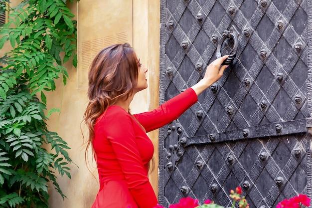 Mulher jovem bate na grande porta de ferro antiga do lado de fora.