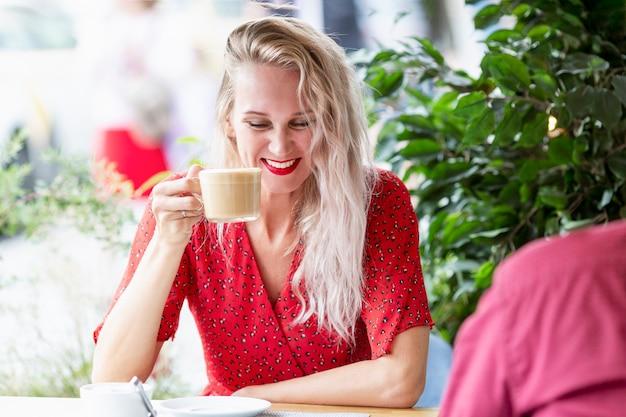 Mulher jovem bebe café e ri. loira linda com cabelo comprido em um vestido vermelho no terraço de um café de verão.