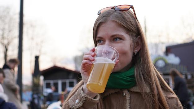 Mulher jovem bebe cerveja light, comida de rua e praça de alimentação