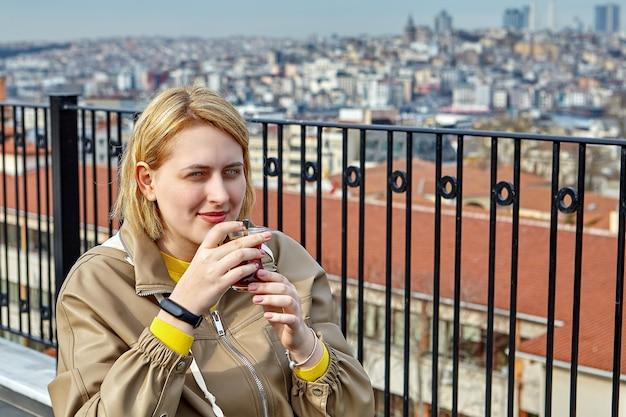Mulher jovem bebe chá quente no telhado do hotel com vista para a paisagem urbana de istambul, na turquia