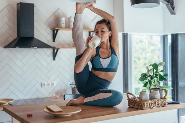 Mulher jovem bebe leite e faz exercícios de alongamento.