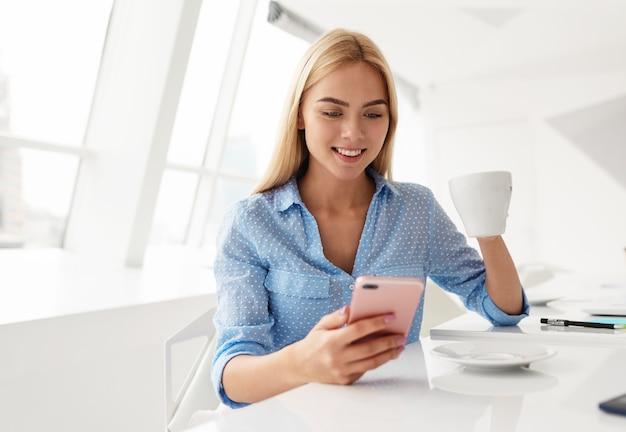 Mulher jovem bebe uma xícara de chá enquanto verifica o telefone celular