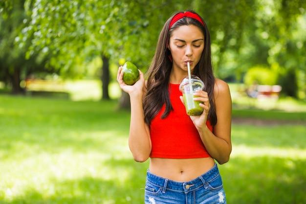Mulher jovem, bebendo, abacate, smoothie, em, copo plástico, em, ao ar livre