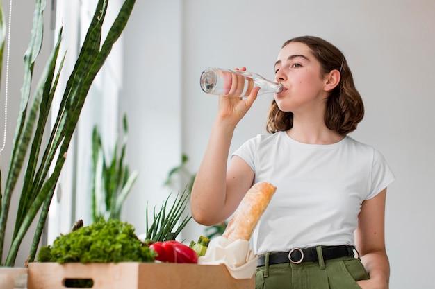 Mulher jovem bebendo água em casa