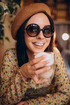 Mulher jovem bebendo café com leite em um café