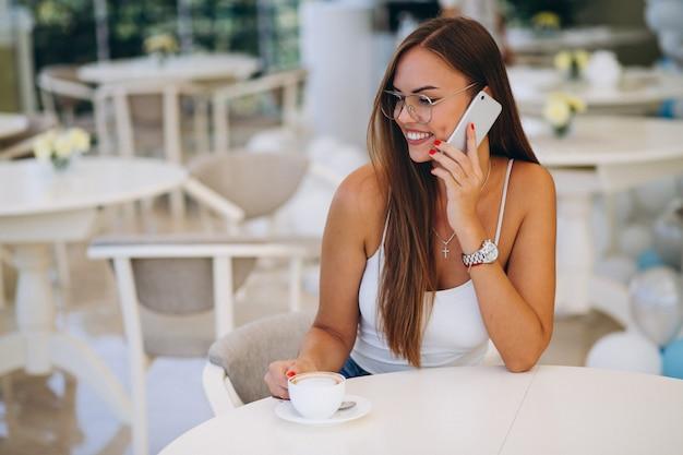 Mulher jovem, bebendo, chá, e, usando, telefone