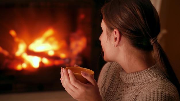 Mulher jovem bebendo chá quente e se aquecendo na lareira na lareira à noite em casa