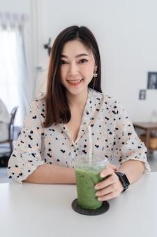 Mulher jovem bebendo chá verde com leite em um café