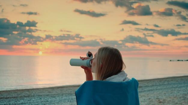 Mulher jovem bebendo em uma caneca térmica e sentada na praia antes do nascer do sol, vista traseira