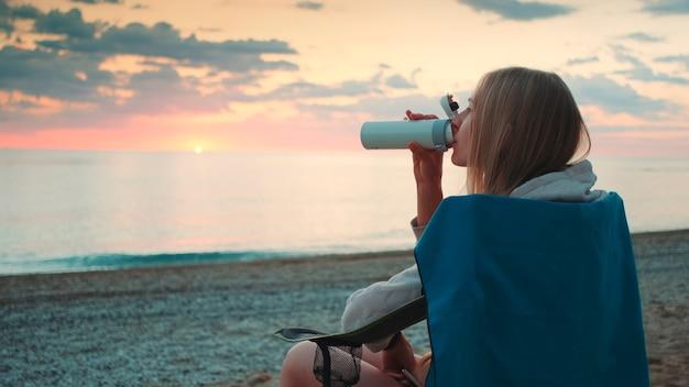 Mulher jovem bebendo em uma garrafa térmica e sentada em cadeiras de camping na vista de perfil da praia