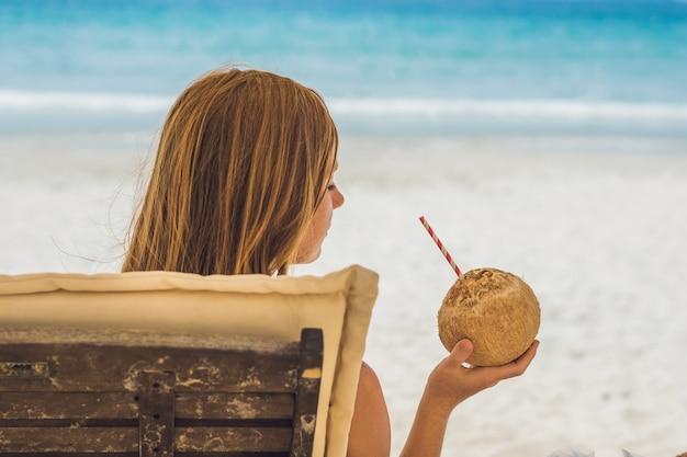 Mulher jovem bebendo leite de coco em uma espreguiçadeira na praia