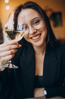 Mulher jovem bebendo vinho branco em um restaurante