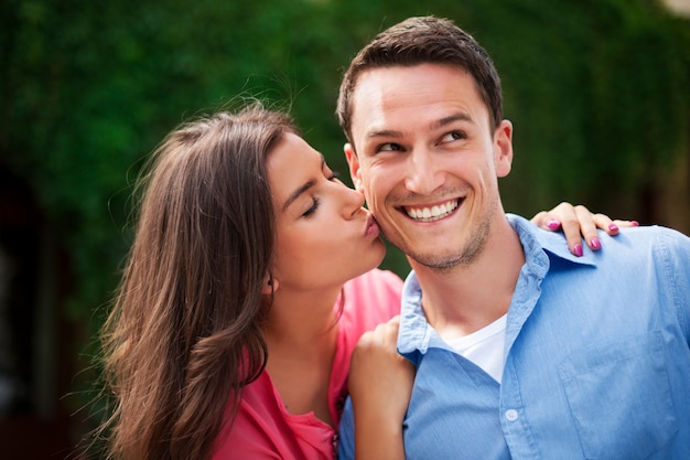 Mulher jovem beijando o namorado na bochecha