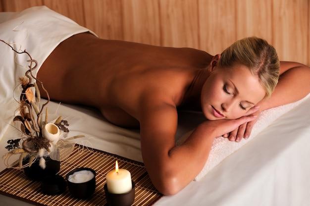 Mulher jovem beleza relaxando no salão spa - vista de alto ângulo