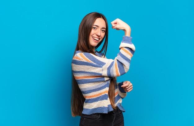 Mulher jovem, bem casual, feliz, satisfeita e poderosa, flexionando a forma e bíceps musculosos, parecendo forte depois da academia