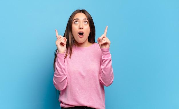 Mulher jovem, bem casual, parecendo chocada, surpresa e boquiaberta, apontando para cima com as duas mãos para copiar o espaço