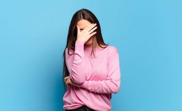 Mulher jovem, bem casual, parecendo estressada, envergonhada ou chateada, com dor de cabeça, cobrindo o rosto com a mão