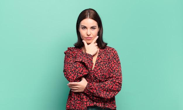 Mulher jovem, bem casual, parecendo séria, atenciosa e desconfiada, com um braço cruzado e a mão no queixo, opções de peso