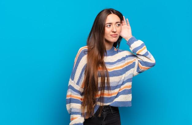 Mulher jovem, bem casual, parecendo séria e curiosa, ouvindo, tentando ouvir uma conversa secreta ou fofoca, bisbilhotando