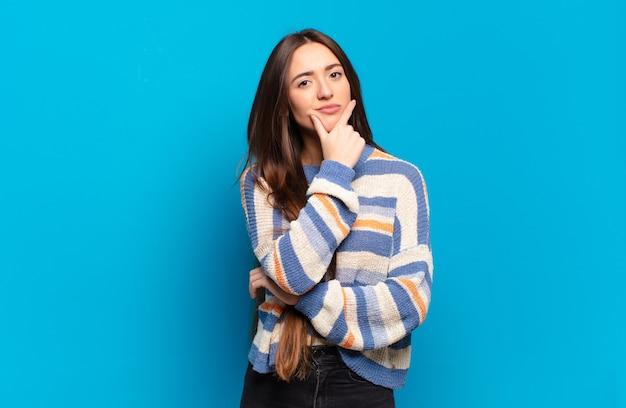 Mulher jovem, bem casual, parecendo séria, pensativa e desconfiada, com um braço cruzado e a mão no queixo, opções de peso