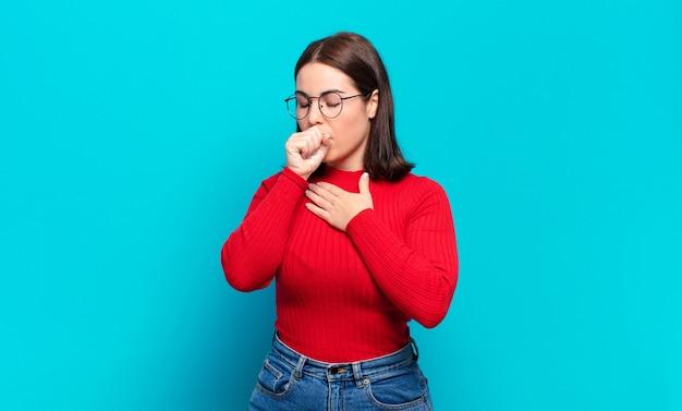 Mulher jovem, bem casual, sentindo-se mal, com dor de garganta e sintomas de gripe, tosse com a boca coberta