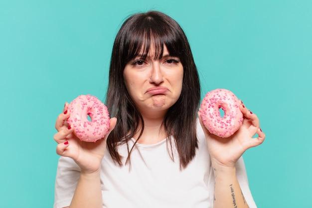 Mulher jovem, bem curvilínea, com expressão triste e segurando uma rosquinha