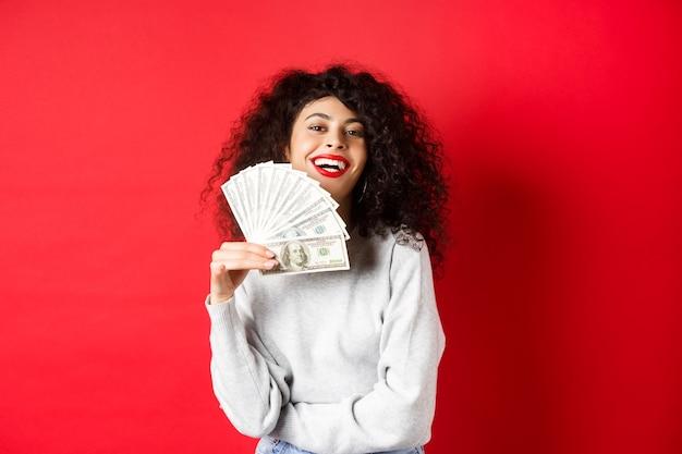 Mulher jovem bem sucedida dispensando notas de dólar e sorrindo satisfeito. menina rica mostrando dinheiro, em pé sobre a parede vermelha.