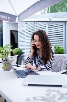 Mulher jovem bem sucedida sorridente, falando ao telefone, trabalhando em um laptop no terraço, garota em um café em uma reunião de negócios. conceito de negócios