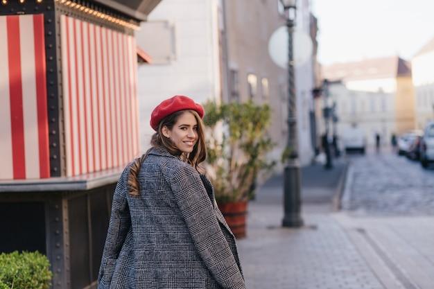 Mulher jovem bem vestida olhando para trás enquanto caminhava pela rua no início da manhã