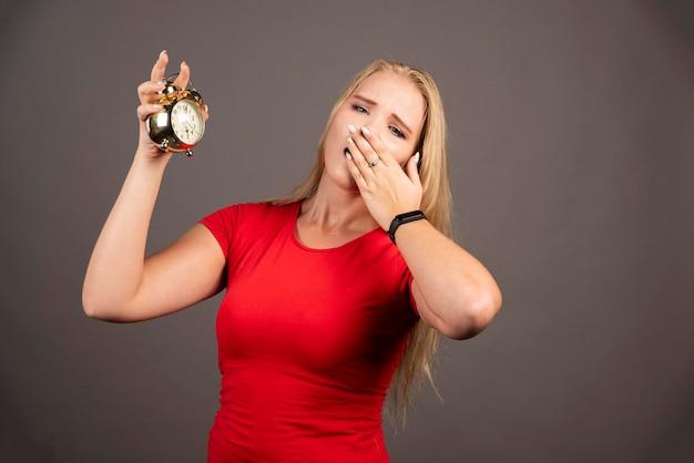 Mulher jovem bocejando em fundo escuro. foto de alta qualidade