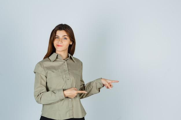 Mulher jovem bonita apontando para a direita, curvando os lábios na camisa e parecendo indecisa. vista frontal.