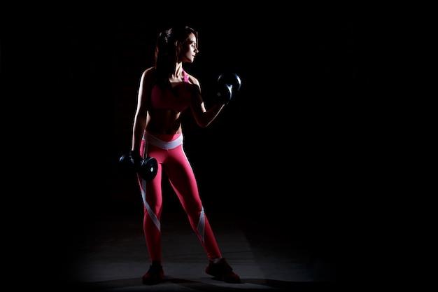 Mulher jovem bonita aptidão que treinamento no ginásio.