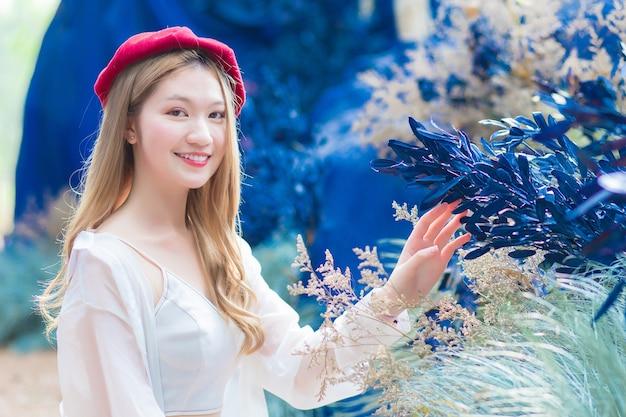 Mulher jovem bonita asiática está se senta e olha para a flor azul no jardim natural do café.