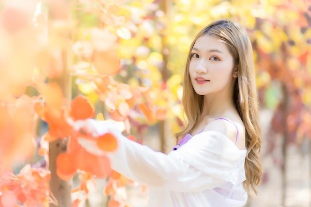 Mulher jovem bonita asiática fica e sorri entre a floresta de laranja em tema natural.