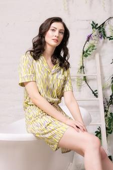 Mulher jovem bonita com beleza natural, sentada na banheira com seu macacão amarelo.