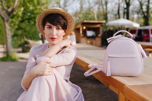 Mulher jovem bonita com chapéu e lábios vermelhos descansando ao ar livre, abraçando suavemente o joelho