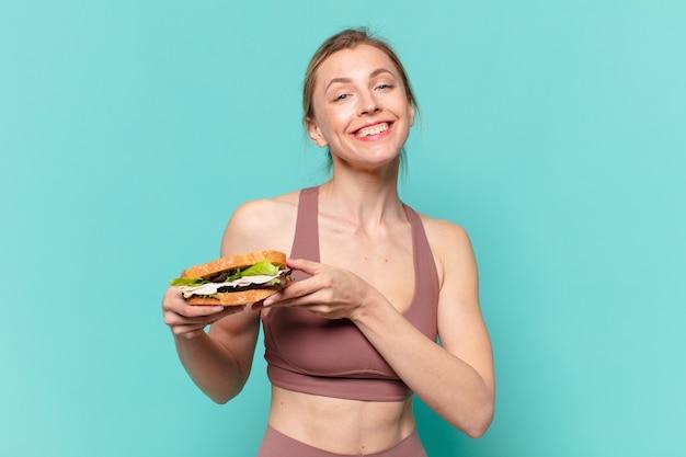 Mulher jovem bonita com expressão de felicidade e segurando um sanduíche
