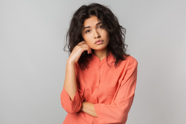 Mulher jovem bonita com expressão facial melancólica, blusa laranja, isolada, emoção triste,