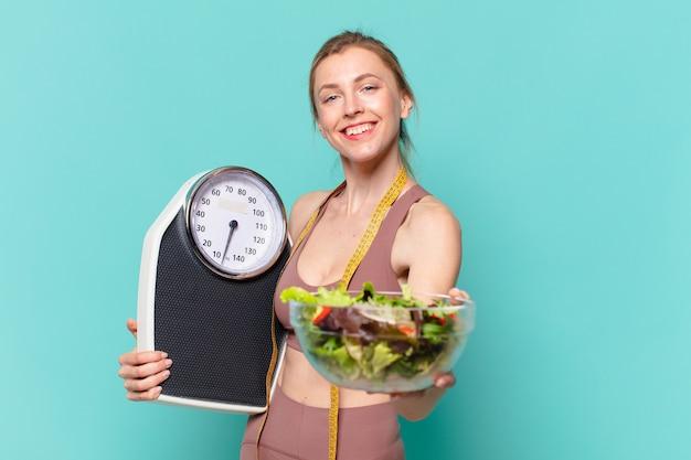 Mulher jovem bonita com expressão feliz e segurando uma balança e uma salada