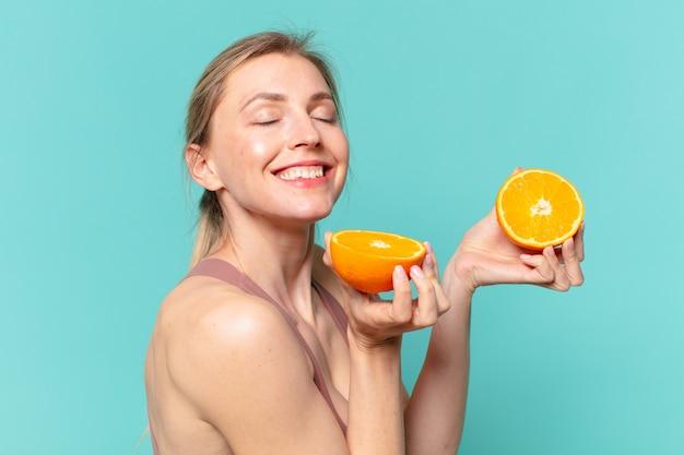 Mulher jovem bonita com expressão feliz e segurando uma laranja