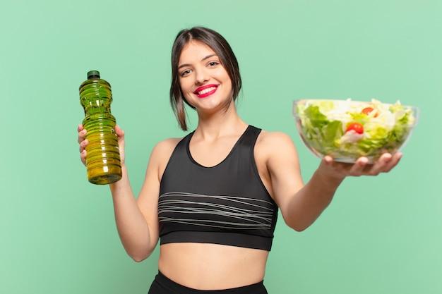 Mulher jovem bonita com expressão feliz e segurando uma salada