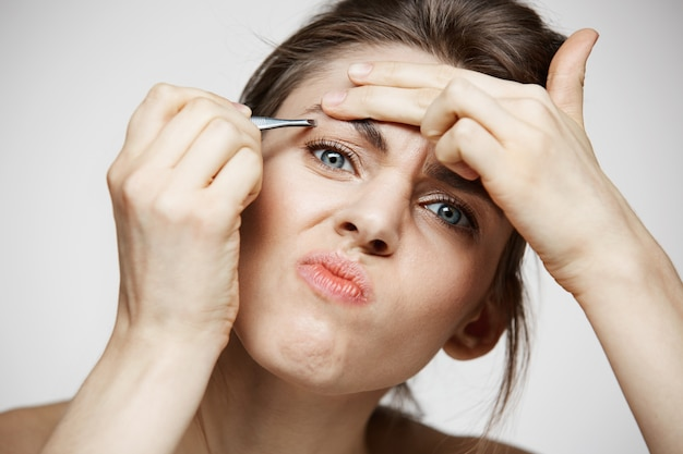 Mulher jovem bonita com sobrancelhas de tweeze pele limpa perfeita, fazendo careta. beleza e spa.