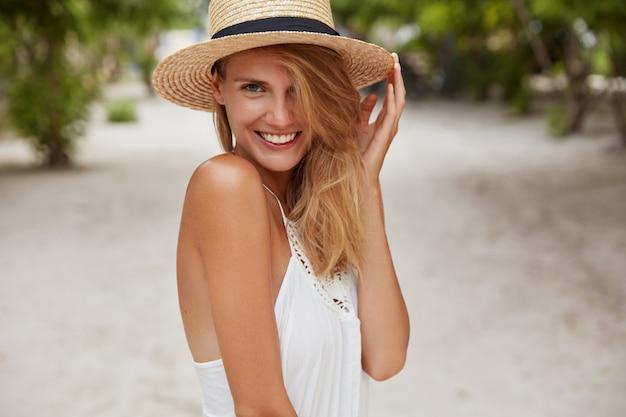 Mulher jovem bonita com sorriso brilhante, pele bronzeada saudável e aparência atraente, gosta de descanso de verão em lugar paradisíaco, usa chapéu de palha, sorri agradavelmente. conceito de pessoas, beleza e descanso sazonal