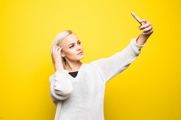 Mulher jovem bonita com suéter branco faz selfie em seu smartphone em amarelo
