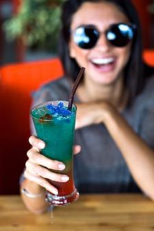 Mulher jovem bonita comemora com doce coquetel alcoólico frio, hora da festa de verão. cores pastel em tons.